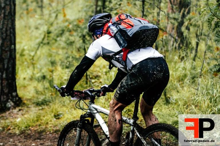 Dreckiger Mountainbiker faehrt im Wald mit Rucksack