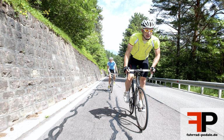 Rennradfahrer faehrt stehend bergauf mit Helm und gelbem Trikot
